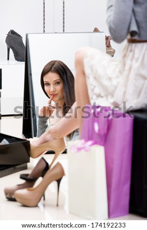 Reflection of woman sitting on chair and trying on new footwear in the shop - stock photo