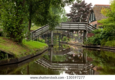 Reflection of Wooden Bridges on a Canal in Giethoorn of Netherlands. - stock photo