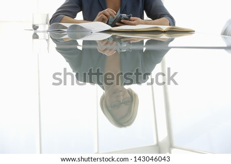 Reflection of young businesswoman using mobile phone on conference table - stock photo
