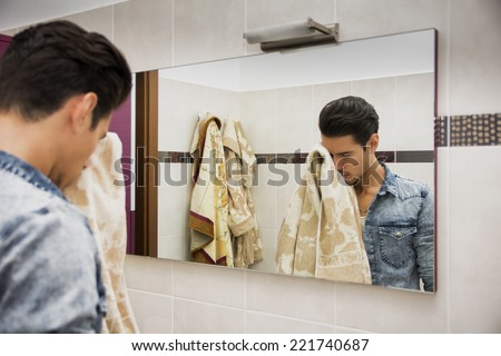 Reflection of Young Man Drying Face with Towel in Mirror as Part of Daily Hygiene Routine - stock photo