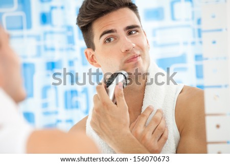 Reflection of young man in mirror shaving with electric shaver - stock photo