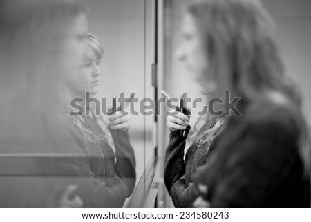Reflection of young women in window, monochrome  - stock photo