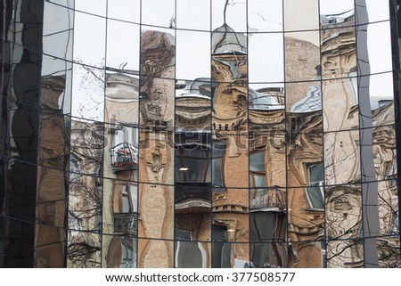 Reflection old building in mirror windows. - stock photo