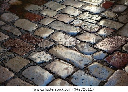 Reflection on paving stones in medieval town - stock photo