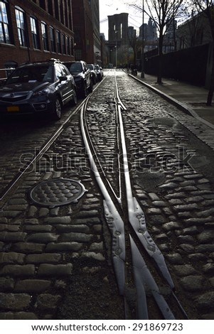 Reflection on railway at cobblestone street in DUMBO, leading to the Brooklyn Bridge, New York City, New York - stock photo