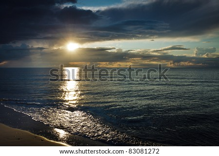 Reflection on sea at sunset over dynamic sky - stock photo