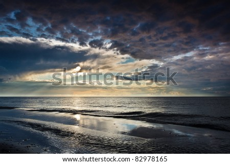 Reflection on the sand over dynamic sky - stock photo