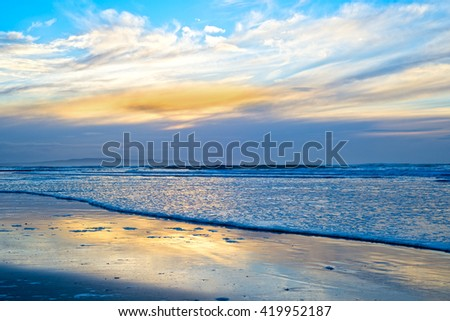 reflections and calm waves crashing onto the beach at ballybunion in ireland - stock photo