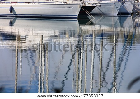 reflections in the calm water sailing boats - stock photo