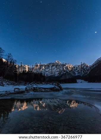Reflections in the frozen lake at night - stock photo