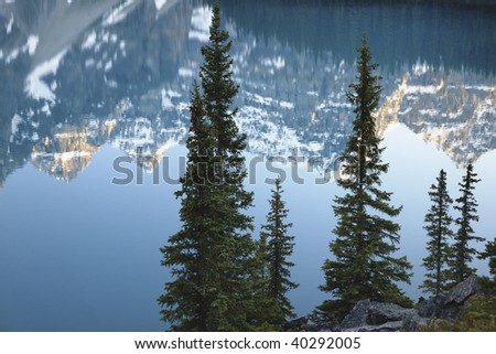Reflections in the turquoise colored waters of Moraine Lake in the Valley of Ten Peaks in Banff National Park, Alberta Canada. - stock photo