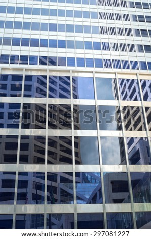 reflections of corporate building off glass skyscraper windows of modern architectural style abstract - stock photo