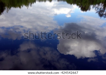 reflections of tranquil blue sky with white clouds on water - stock photo