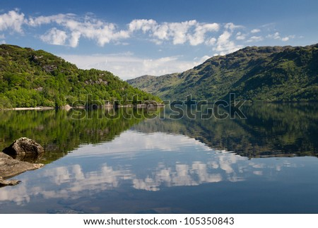 Reflections of trees and clouds on Loch Lomond, Scotland, United Kingdom - stock photo