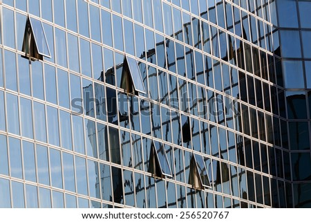 Reflections on modern building's  blue and green glass facade - stock photo