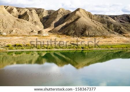 Reflective autumn river - stock photo