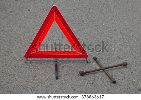 Reflective car warning triangle and tool on the road. Driving and safety themes - stock photo