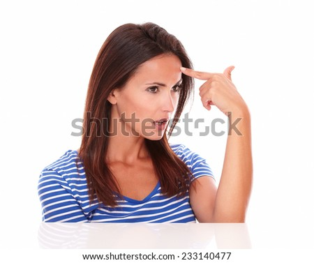 Reflective female looking to her left and pointing to her forehead in white background - copyspace - stock photo