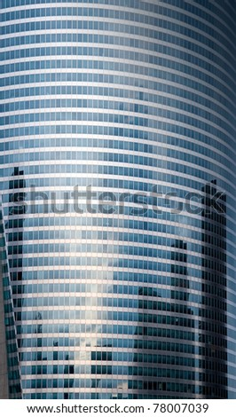 Reflexion of modern builds in windows of rounded office tower - stock photo