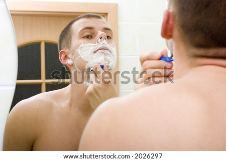 reflexion of shaving young man in the bathroom's mirror - stock photo