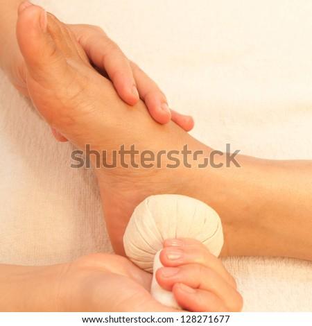 reflexology foot massage, spa foot treatment by ball herb,Thailand - stock photo