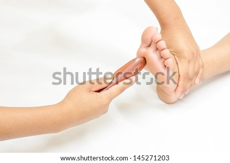 reflexology foot massage, spa foot treatment by wood stick,Thailand.  - stock photo