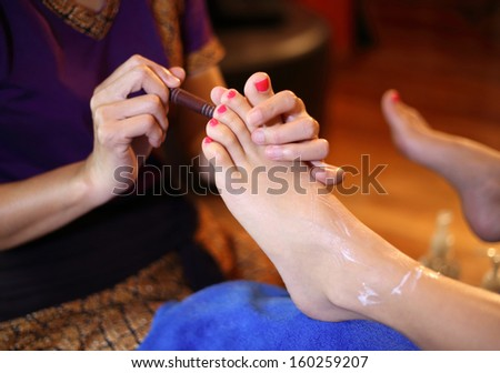 reflexology foot massage, spa foot treatment by wood stick,Thailand  - stock photo