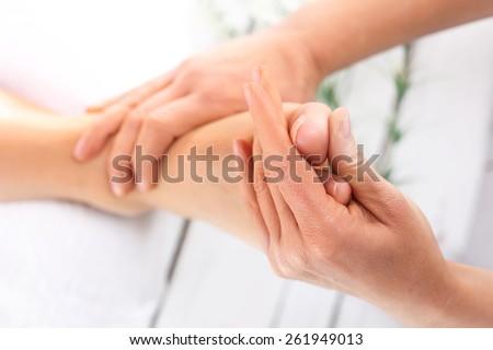 Reflexology. Masseuse massaging woman's foot. - stock photo