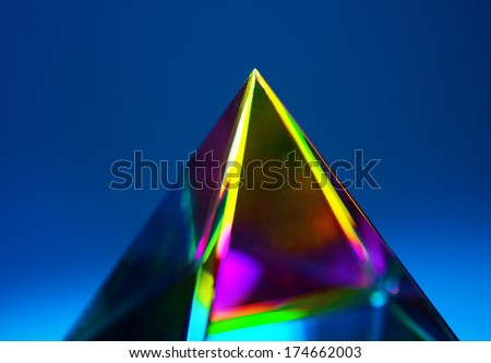 Refractions of light in a glass prism. Focus is on tip - stock photo