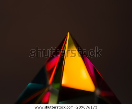 Refractions of light in a glass prism. Shallow depth of field. Focus is on the area little beneath the tip. - stock photo
