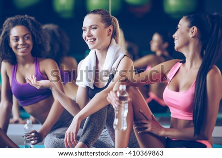 Refreshing after workout. Beautiful young women in sportswear discussing something with smile while sitting on exercise mat at gym - stock photo