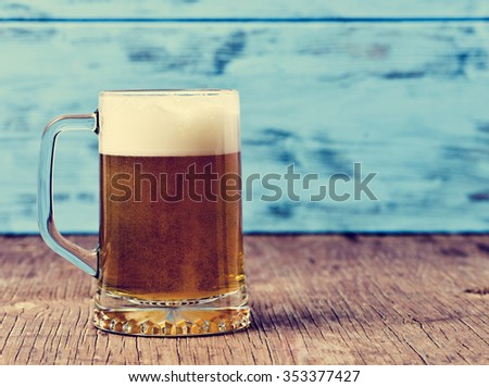 refreshing beer served in a glass mug on a rustic wooden surface, against a blue rustic wooden background - stock photo