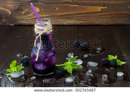 Refreshing blackberry juice in vintage eco style bottle on rustic dark wooden table. Cold summer berry drink with ice and mint. Copy space background. Clean eating - stock photo