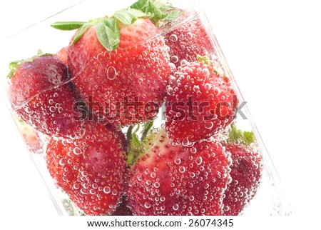 Refreshing carbonated soda poured over fresh red ripe strawberries for a refreshing drink diagonal copy space - stock photo