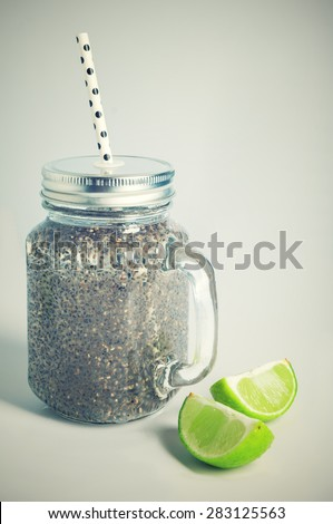 Refreshing chia seeds drink with water, coconut milk and lime in mason jar and white polka dot paper straw. Toned.  - stock photo