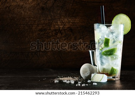 Refreshing Christmas cocktail with a blend of white spirits, mixer and fresh aromatic herbs in a tall glass with ice garnished with tangy lemon, dark background with copyspace - stock photo