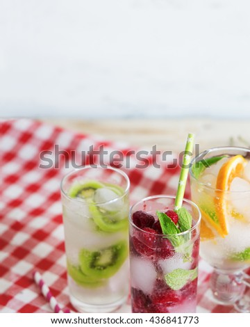 Refreshing cocktails with juicy fruits, fresh mint and ice in a glass. Close-up. - stock photo