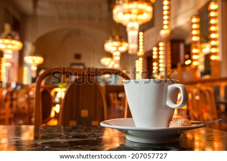 Refreshing coffee with a backdrop of Art Deco lighting in Prague cafe, Czech Republic. - stock photo