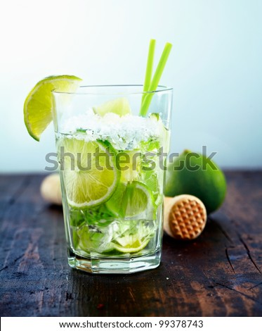 Refreshing cold Caipirinha with fresh lime slices and ice. - stock photo
