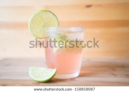 refreshing cold cocktail with fresh lime slices and ice on wooden background - stock photo