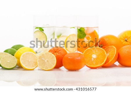 Refreshing cold drinks with low calories; Citrus fruits and glasses of ice-cold mineral water against white background; Thirst quencher in summer heat; Flavored mineral waters - stock photo