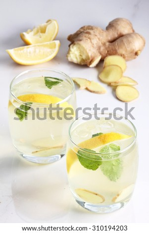 refreshing flavors of lemonade, ginger, and mint in a glass on white marble top table - stock photo