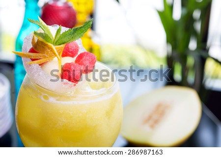 refreshing glass of bright juicy melon smoothie or lemonade with ice on a table at a restaurant with the decor of the bright dishes and pieces of melon - stock photo
