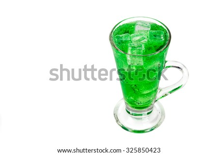 Refreshing green fizzy soft drink with ice in transparent glass. - stock photo