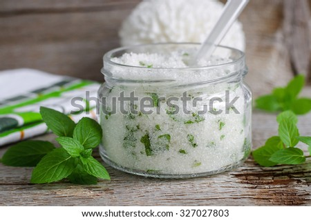 Refreshing homemade sugar scrub with vegetable oil, chopped mint leaves and essential mint oil - stock photo