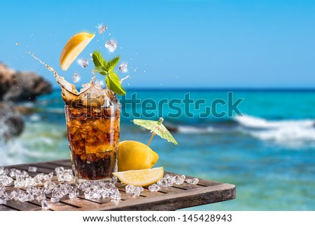 Refreshing iced rum and soda tropical cocktail garnished with fresh lemon and leaves of mint with splashing ice served on a wooden table overlooking a blue ocean - stock photo