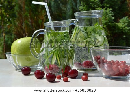 Refreshing infused water with arugula and cucumber slices. Homemade detox cocktail in glass jugs and fresh natural ingredients are on a table in a garden. Cooking outdoor. Summertime. - stock photo