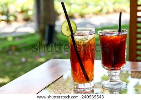 Refreshing lemon iced tea and black tea in the garden - stock photo