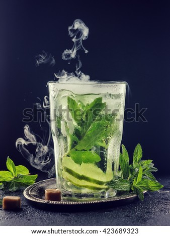 refreshing lemonade with mint and lime in a transparent glass on a dark background. dry ice, Studio shot - stock photo