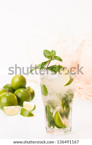 Refreshing Mojito cocktail with limes and straw hat background - stock photo